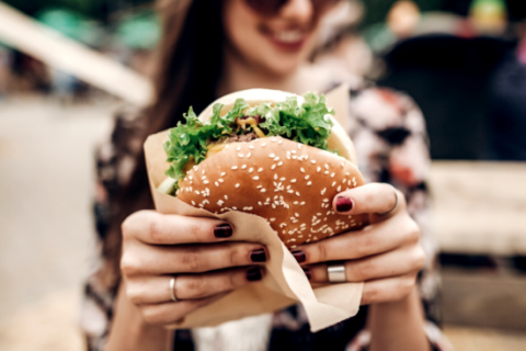 Woman holds up a large hamburger