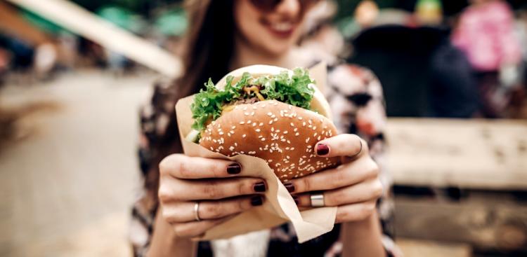 Woman holds up a large hamburger
