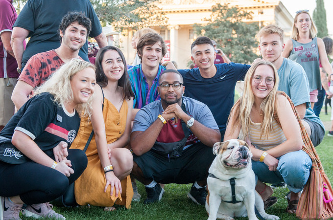 Group of diverse alumni gather around Addie, the bulldog mascot.