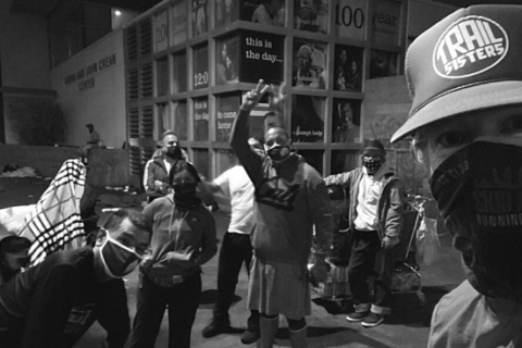 Brian Charest peers into view with a hat and facial bandana while a crowd of runners are in the background at night in Skid Row