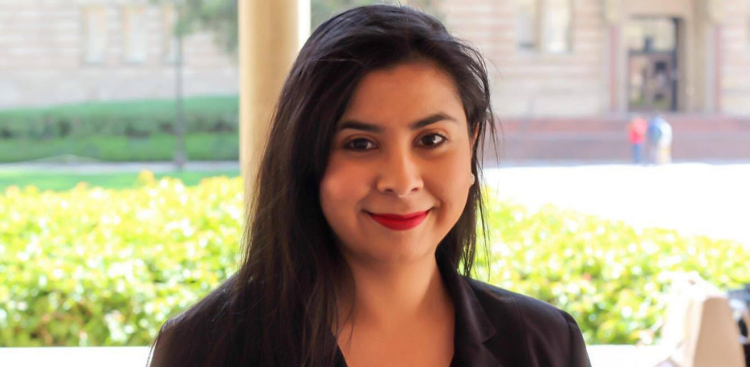 Maria Quiroz smiles with bright red lipstick and straight, brown hair. She is wearing a black blazer.