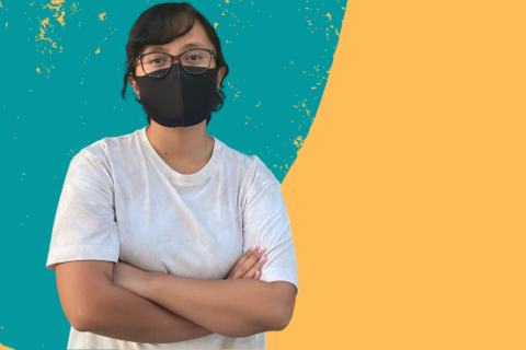 Romina-marie Baronia stands with arms folded, as her face is covered with a black mask.