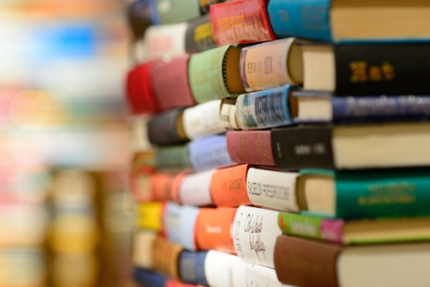A pile of multicolor hard cover books.