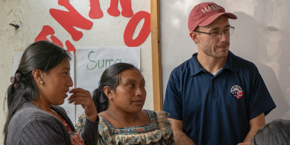 A man in a Peace Corps polo looks on in a classroom of Latin American women.