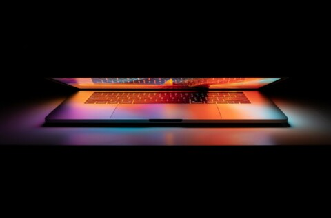 Image of partially open laptop on black background