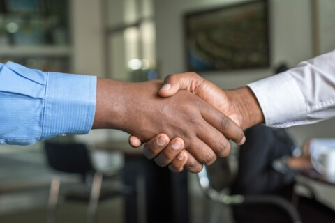 handshake between two people in dress shirts