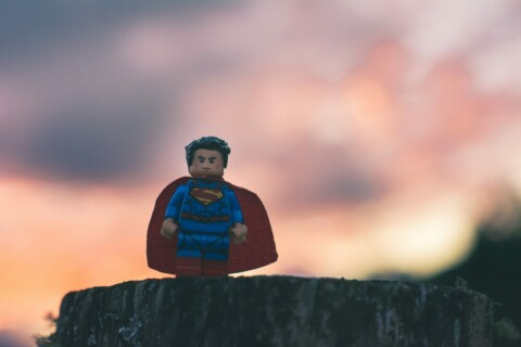 Lego Superman on a tree stump, sunset in the background
