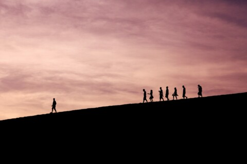 People walking along a sunset with one figure clearly leading the others