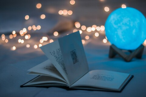 Open book surrounded by twinkling lights