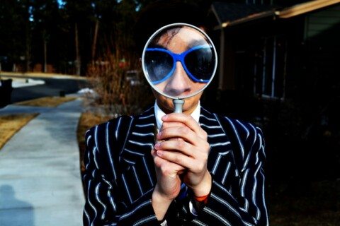 Woman holding a magnifying glass up to her face