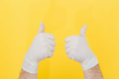 Two hands in gloves giving the thumbs up against a yellow background