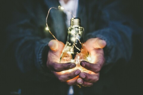 Person holding lightbulb lit up with smaller lights in hands