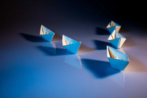 One paper ship leading four others in a triangle formation