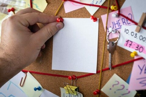 Blank Post-it being pinned on a bulletin board