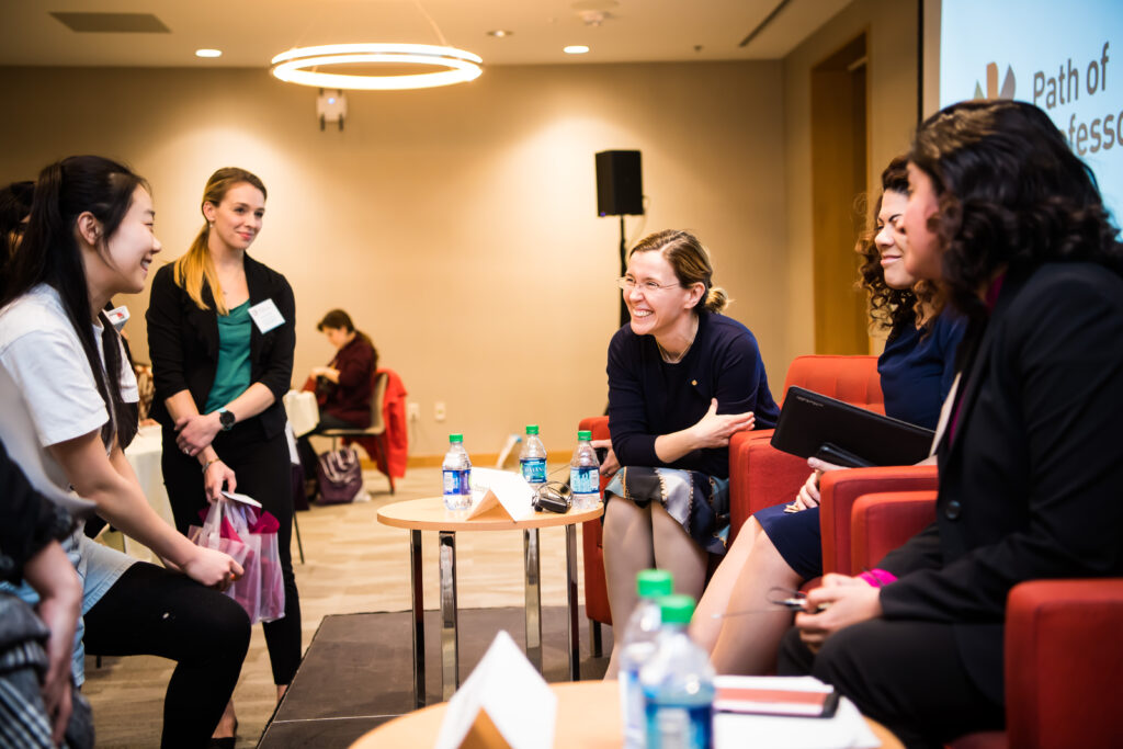 Speakers and attendees laugh together at the 2019 Path of Professorship conference.