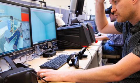 man at computer setting up a virtual reality game