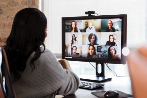 A person looks at a panel of people on a monitor.
