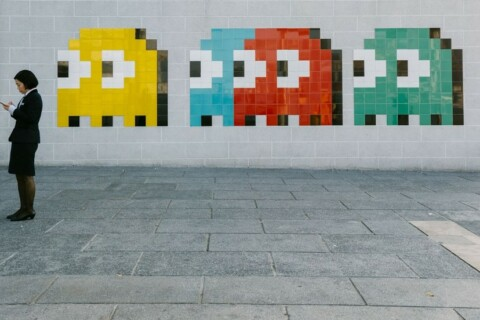 someone standing in front of wall decorated with pac man ghosts