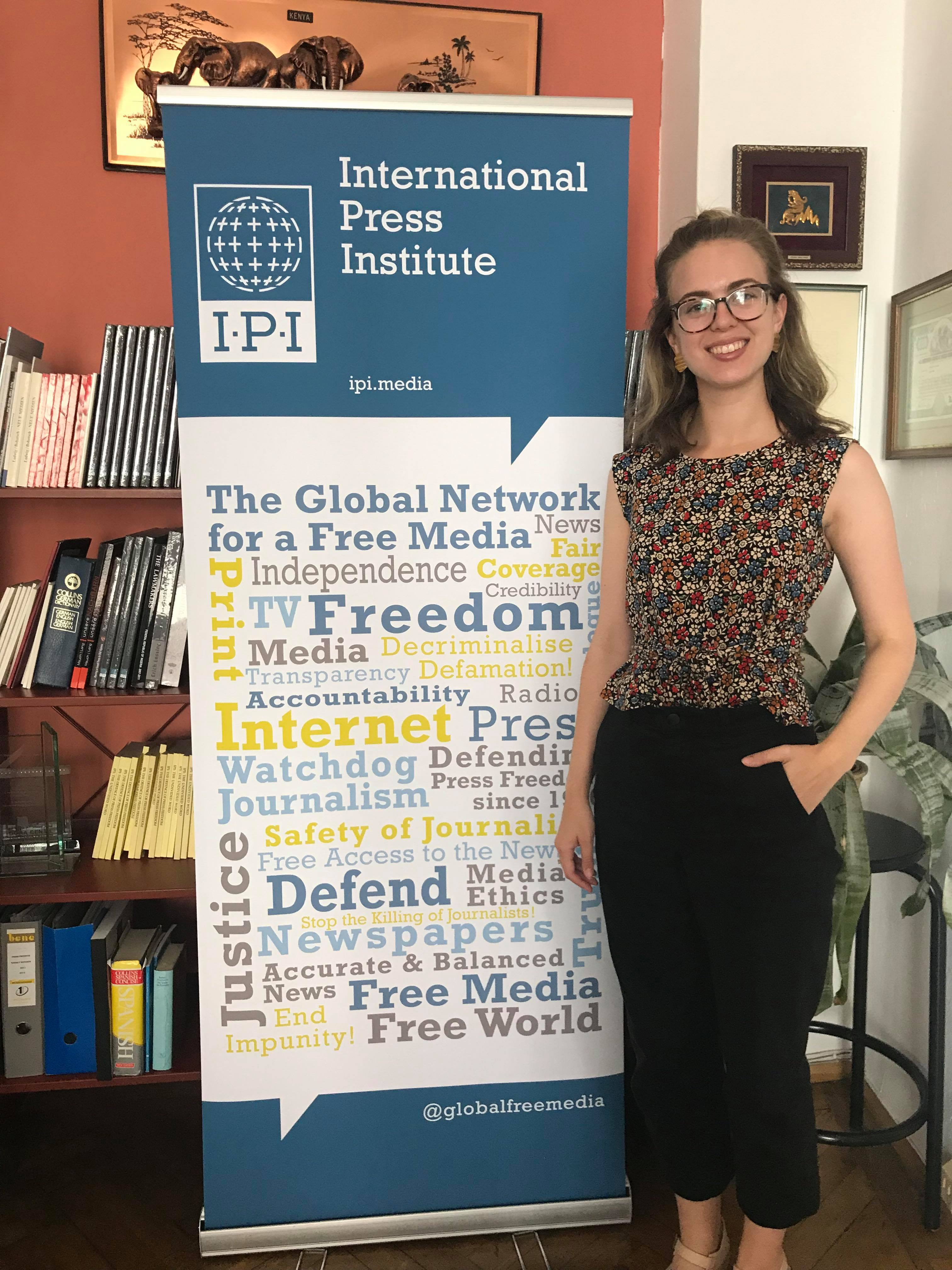 Abigail Gipson stands next to a poster for the International Press Freedom Institute.