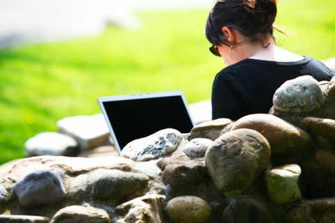 """Student studying on her laptop on campus. Photo by Dennis Wise."""