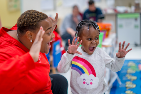 Preschool teacher and preschool-aged girl playing and roaring together, with smiling, open mouths and hands stretched up