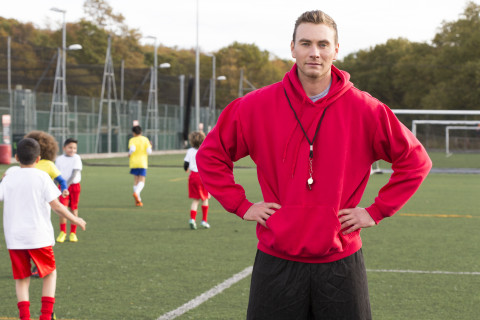 Soccer coach stands looking direct at the camera while standing with his hands on his waist. Children can be seen wearing sports clothing in the background
