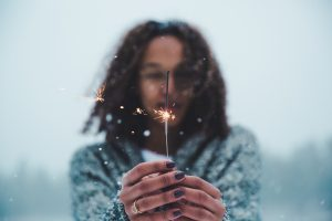 A woman holding a sparkler in the snow.