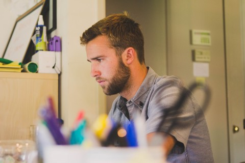 adult man with beard in room dorm concentrating thinking college