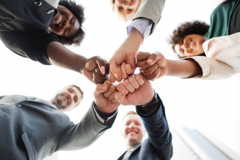 diverse people wearing suits fits bumping teamwork