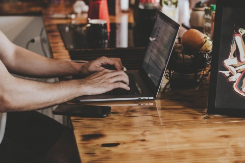 person-in-front-of-laptop-on-brown-wooden-table-2115217