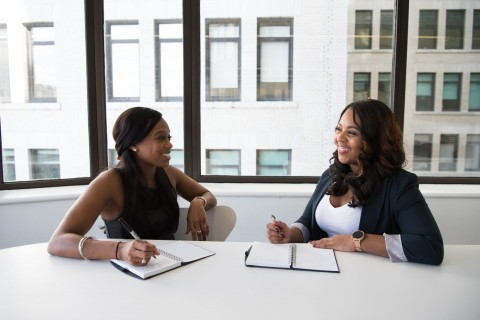 two african american black women in business setting talking