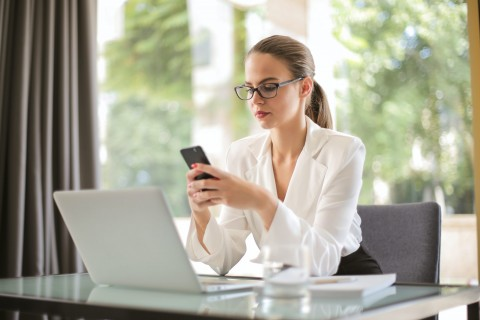 women in business attire using phone and laptop
