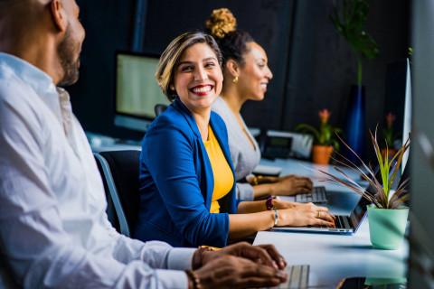 Woman smiling at man while using laptop
