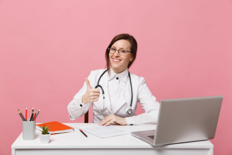 Beautiful female doctor sits at desk works on computer with medical document in hospital isolated on pastel pink wall background. Woman in medical gown glasses stethoscope. Healthcare medicine concept