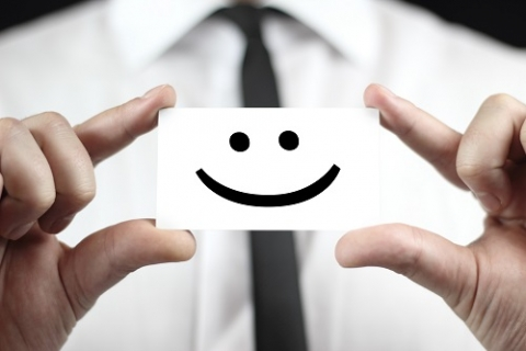 A person slightly blurred in the background holds a business card-sized piece of paper showing a smiley face, which is in the foreground.