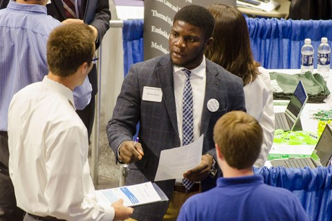Students speaking with an employment recruiter at a career fair.