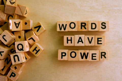 The phrase 'words have power' spelled out with Scrabble tiles.