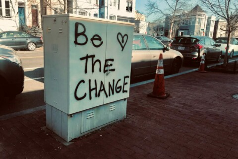 Be The Change spray painted on a utility cabinet.