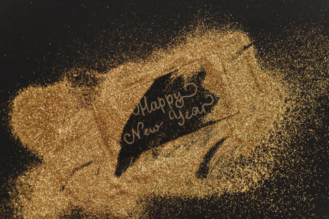 Fine golden glitter against a pitch black background. In the center, written in the golden glitter, are the words Happy New Year