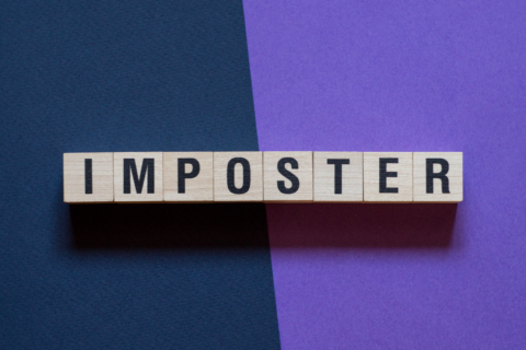 Wooden scrabble tiles spell out the word IMPOSTER on a blue and purble background.