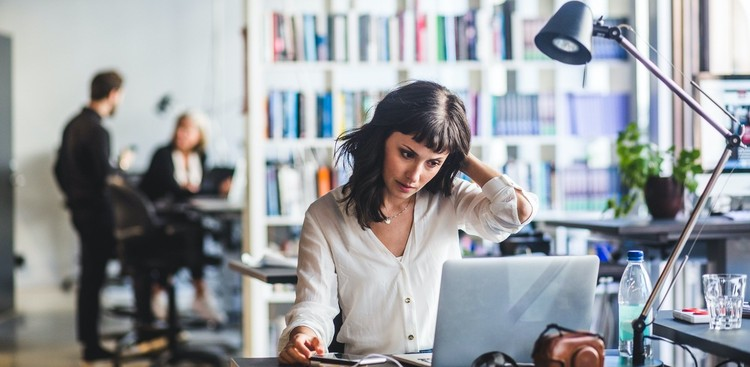 A young woman sits at her office laptop, scratching her head in distress. In the backfround, two other employees hold a discussions behind a bookshelf.