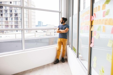 A young man with a beared and a man bun stares out a large glass window overlooking a city. Behind him, a whiteboard style wall is lined with sticky notes.