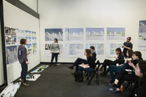 A group of students sit in folding chairs in white walled room. Drawings hang on the wall, and others are on the floor in front of the walls. A professor stands at the front of the room. criticing the art. The artist, a young woman ina grey sweater, stands next to the art, listening to the critique and smiling.