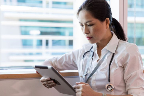 A doctor reads her tablet device