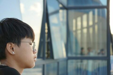 Asian American looking toward a glass building façade