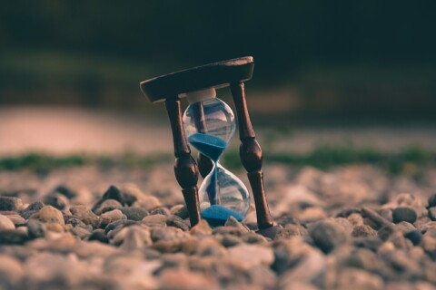An hourglass in a pebble road because time is of the essence