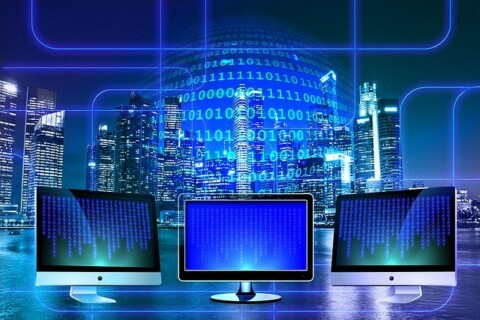 Abstract image with three computer monitors and a sphere of data in front of a nighttime urban skyline shot