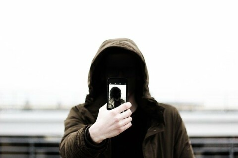 A person in a hoodie, with their face completely obscured, takes a selfie that duplicates this erasure of their face