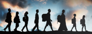 Silhouette photo of refugees walking in the same direction and carrying their belongings