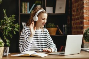 Joyful young female in wireless headphones waving wand greeting to screen while sitting at table and having video chat with business partners using laptop against blurred dark interior of comfortable loft office